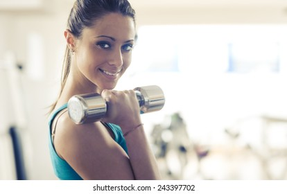 Attractive smiling woman doing weightlifting exercise at gym with dumbbells.
