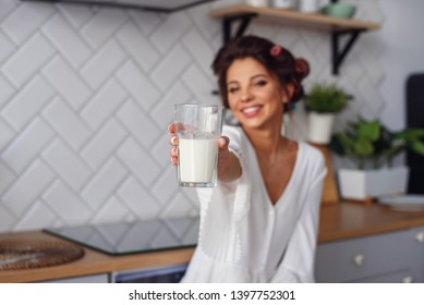 Attractive smiling woman gives to the camera a glass of fresh milk in the stylish cozy kitchen at the morning. Pretty healthy girl holds a glass of fresh milk on foreground.