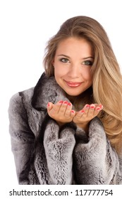 Attractive smiling woman in a gray coat with open hands palm for product