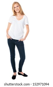 Attractive smiling woman with long blond hair in jeans standing with her hands in her pockets looking at the camera, isolated on white