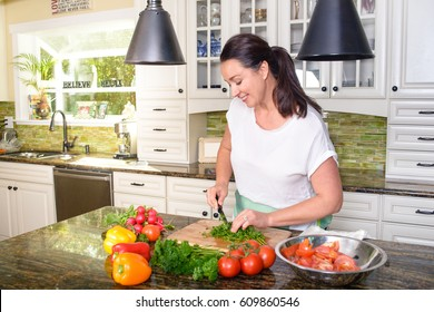Attractive smiling woman making salad in her sunny kitchen