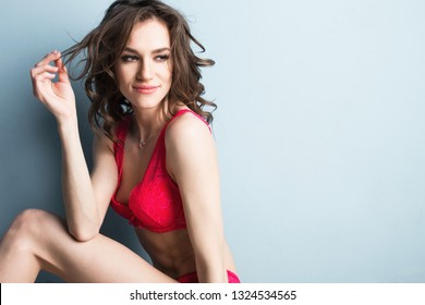 Attractive smiling woman in pink lingerie with fashion hairdo. Studio shoot.