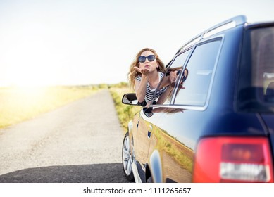 Attractive smiling woman sends an air kiss from the car window.