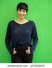 Attractive smiling woman with short hair standing against green wall.