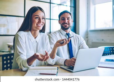 Attractive smiling woman speaking positive history about happening with colleague during break from searching information via modern devices, successful colleagues enjoying friendly entrepreneurship