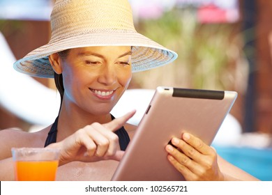 Attractive smiling woman with straw hat using tablet computer in pool