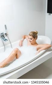 attractive and smiling woman taking bath with foam in bathroom
