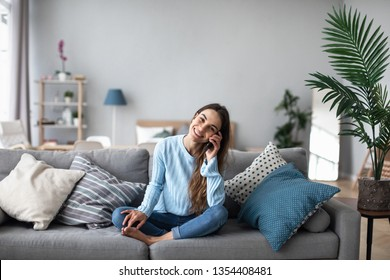 Attractive smiling woman talking on the phone at home. Technology, communication and coziness concept.