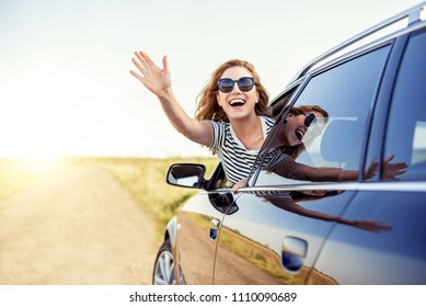 Attractive smiling woman waving her hand from the car window.