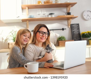 Attractive smiling woman working with little adorable daughter and kitten at home