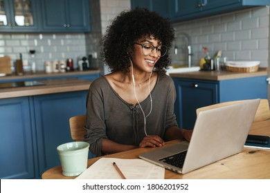 Attractive smiling young african woman on a video call with colleagues, sitting on a kitchen with laptop computer
