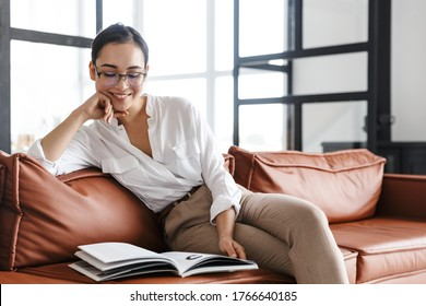 Attractive smiling young asian business woman relaxing on a leather couch at home, reading a magazine