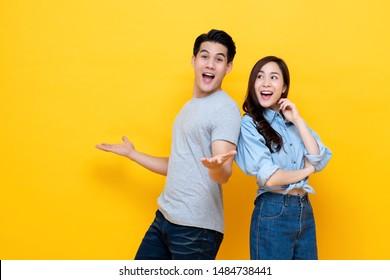 Attraktiv lächelndes junges asiatisches Paar, das glücklich und erstaunt ist einzeln auf gelbem Studiohintergrund