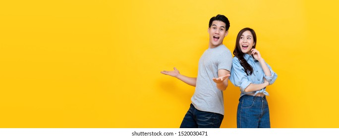 Attractive smiling young Asian couple being happy and amazed isolated on yellow banner background with copy space
