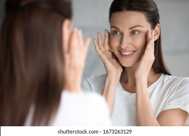 Attractive smiling young brunette woman looking at mirror, touching face. Happy 30s lady satisfied with moisturized soft skin condition after professional cosmetology services, skincare concept.