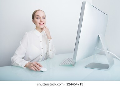 Attractive smiling young business woman working on computer in the office at the desk looking at the camera