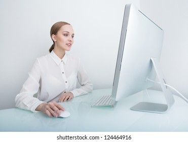 Attractive smiling young business woman working on computer in the office at the desk