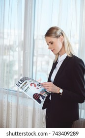 attractive smiling young businesswoman reading magazine