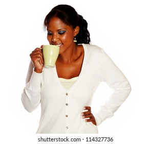 Attractive smiling young female drinking tea mug against white background