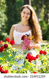 Attractive smiling young female gardening with roses in yard