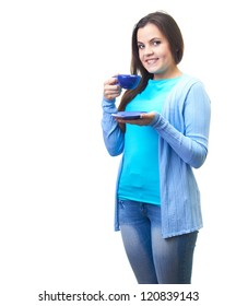 Attractive smiling young woman in a blue shirt holding blue cup and blue saucer. Isolated on white background