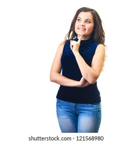 Attractive smiling young woman in a blue shirt and blue jeans holding her finger on her chin and looks into the upper-right corner. Isolated on white background