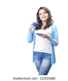 Attractive smiling young woman in a blue shirt holding blue cup and saucer and looks in the upper-left corner. Isolated on white background