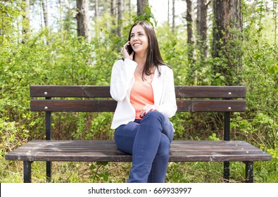 Attractive smiling young woman dressed casually talks with her smartphone sitting on a wooden bench in the forest. Modern lifestyle using portable mobile devices everywhere people go. Talking to phone