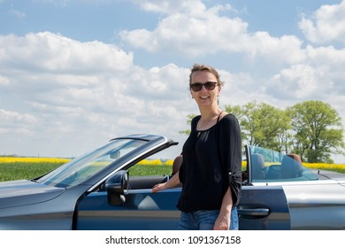 Attractive smiling young woman standing next  luxury convertible car. she looks at camera.