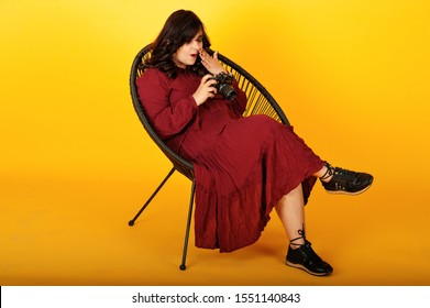 Attractive south asian woman in deep red gown dress posed at studio on yellow background sitting on chair with old vintage photo camera.