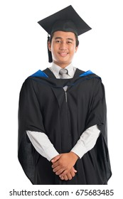 Attractive Southeast Asian male university student in graduation gown, standing isolated on white background.