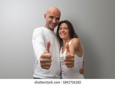Attractive Spanish couple doing thumb up gesture at the same time