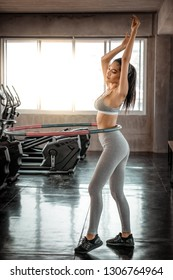 attractive sport asia woman rotates hula hoop in sport gym