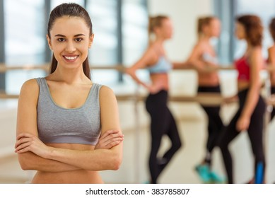 Attractive sport girl looking at camera and smiling while standing in fitness class, in the background girls talking