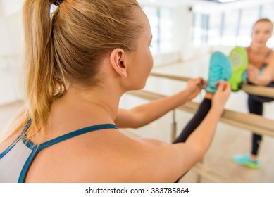 Attractive sport girl smiling and lacing training shoes while stretching the body in fitness class