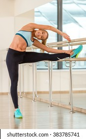 Attractive sport girl smiling and looking at camera while stretching the body in fitness class