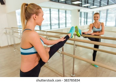 Attractive sport girl smiling and looking in the mirror while stretching the body in fitness class
