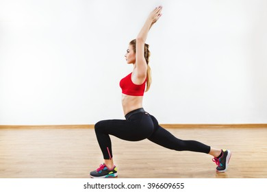 Attractive sportive girl wearing snickers, black leggings and red short top doing yoga warrior pose, fitness, white wall and wooden floor at background.