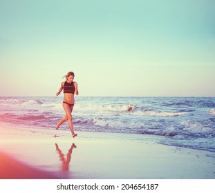Attractive sports girl runs on sand waves touching, sky reflected on the sand,  fitness and healthy lifestyle concept