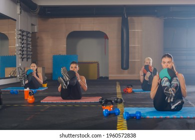 Attractive sports girls practicing abs exercise with med ball in a group fitness workout
