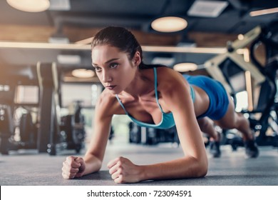 Attractive sports woman in gym is doing plank exercise.