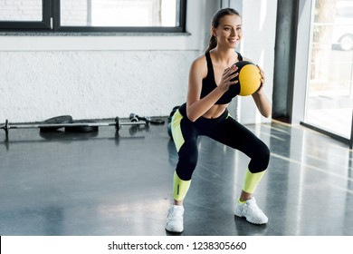 attractive sportswoman doing squats with medicine ball at gym