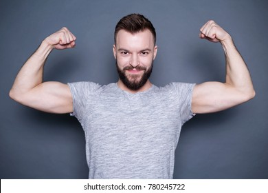 An attractive sporty bearded man in a T-shirt shows his biceps.
