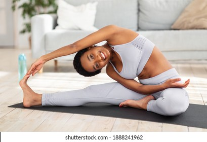 Attractive sporty black woman doing warming up stretching exercses on yoga mat in her home gym. Positive millennial lady bending to her leg, working out muscles flexibility