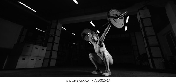 Attractive sporty crossfit woman performing overhead squats with a heavy barbell at the gym complex fitness overhead performance athlete active lifestyle weightlifting bodybuilder