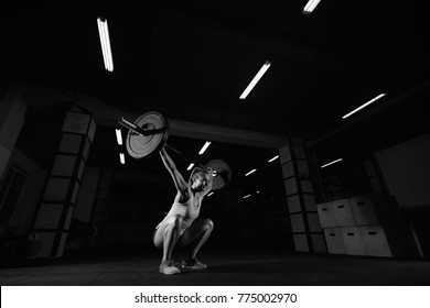 Attractive sporty crossfit woman performing overhead squats with a heavy barbell at the gym complex fitness overhead performance athlete active lifestyle weightlifting bodybuilder, crossfit