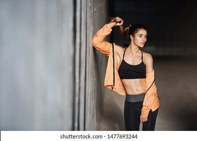 Attractive sporty girl with perfect body wear activewear leggings, lean concrete wall turn aside, smiling pleased and motivated, finish productive outdoor training session, runner prepare to marathon