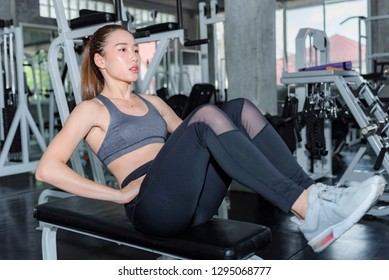 Attractive sporty girl performing sit ups stomach muscle definition in gym.