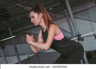 Attractive sporty girl in sports wear holding hands together and squatting in dark gym. Athletic young woman doing squat exercises for buttocks. Sports girl doing exercises in gym. Workout indoors