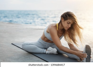 Attractive sporty tanned fit woman wearing sports bra sitting fitness mat stretching, warming-up before outdoors pier jogging along docks during sunset near sea, caring for health, body shape